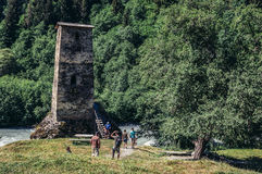 Tower in Georgia. Upper Svanetia, Georgia - July 24, 2015. Tourists visits characteristic Svanetian tower structure called Tower of Love next to road from Mestia Royalty Free Stock Photo