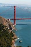 Tower of Golden Gate Bridge  across San Francisco Bay to Oakland. Tower of Golden Gate Bridge and across San Francisco Bay to Oakland framed by cliffs on a sunny Stock Photo