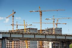 Cranes and building construction. Tower hoisting cranes over building construction Stock Image