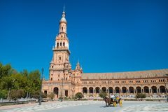Tower and horse and carriage at Spain Square, Plaza de Espana, in Sevilla royalty free stock images