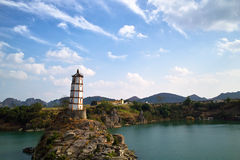 Tower on island in ocean. Scenic view of tower or lighthouse on rocky island in ocean with coastline in background under cloudscape, China Stock Images