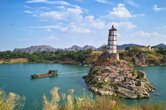 Tower on island in ocean. Scenic view of tower or lighthouse on rocky island in ocean with coastline in background under cloudscape, China Stock Image