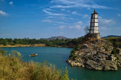 Tower on island in ocean. Scenic view of tower or lighthouse on rocky island in ocean with coastline in background under cloudscape, China Royalty Free Stock Photography