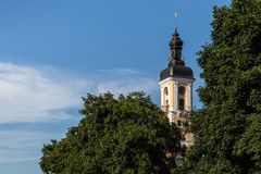 The tower of the Kamianets-Podilskyi town hall, which rises above the green crowns of trees. The tower of the Kamianets-Podilskyi town hall, which rises above stock photo