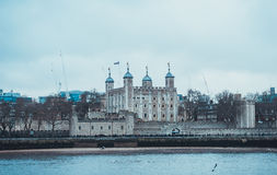Tower of London on Bank of Thames River in London. Waterfront View of Tower of London with Traitor Gate Entrance, a UNESCO World Heritage Site and Famous Tourist Stock Photo