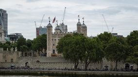 Tower of London over the River Thames in London, England. The Tower of London in London England, view over the River Thames from the South Bank. Construction royalty free stock image