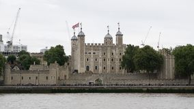 Tower of London in London, England, view from over River Thames. The Tower of London in London England, view from south bank of River Thames. The Tower was built royalty free stock photography