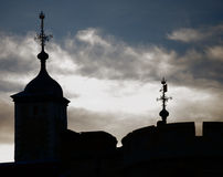 Tower of London silhouetted. A view of the top of the famous Tower of London, silhouetted in sharp contrast against a dramatic sky and clouds Royalty Free Stock Photo