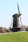 Tower mill The blue heron, Holland. A traditional grain mill just behind the dike, named The Blue Heron Mill, along the river of Waal in the little dutch village Royalty Free Stock Photo
