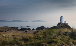 The Tower in the Mist Llanddwyn Island, Anglesey, Wales. The Tower on Llanddwyn Island, Anglesey with sea mists and the Lynn Peninsula, North Wales in the Royalty Free Stock Images