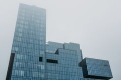 Tower of modern skyscraper glass building in fog or mist Royalty Free Stock Photos