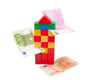 Tower from multi-coloured cubes and banknotes. Tower from multi-coloured cubes and a banknotes on white background Royalty Free Stock Image