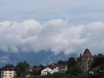 Tower and nice housing estate on hill at cityscape landscape of clouds above european capital Vaduz city Liechtenstein. Stony tower and nice housing estate on stock image