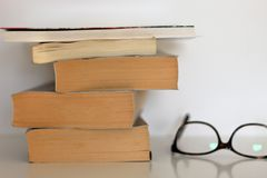 Tower of old books and glasses on white table. Tower of old books and glasses on white table over white background royalty free stock image