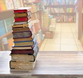 Pile of old books. Tower of old books with open one on wooden shelf over library background stock photo