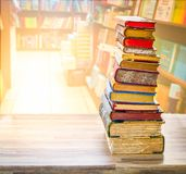 Pile of old books. Tower of old books on wooden shelf over library background stock photo