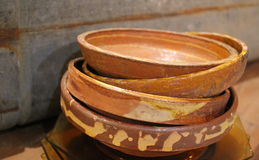 Tower of old vintage antique chipped glazed redware bowls for shabby chic eclectic home decorating Royalty Free Stock Image