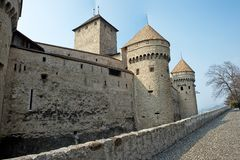 Tower and Parapet of a Medieval Castle. The exterior wall showing the parapet and turrets of a medieval castle with a low wall bordering a cobblestone road in Stock Image
