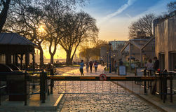 Tower park in sun set. River Thames side walk with people resting by the water. London Stock Photos