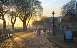Tower park in sun set. River Thames side walk with people resting by the water. London Stock Photography