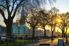 Tower park in sun set. River Thames side walk with people resting by the water. London Royalty Free Stock Image