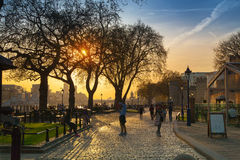 Tower park in sun set. River Thames side walk with people resting by the water. London Stock Images