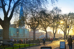 Tower park in sun set. River Thames side walk with people resting by the water. London Royalty Free Stock Photos