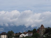Tower and quiet housing estate on hill at cityscape landscape of clouds above european capital Vaduz city Liechtenstein. Stony tower and quiet housing estate on stock image