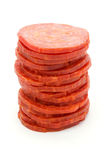 Tower of slices of salami over white. Tower of slices of salami isolated on white Royalty Free Stock Photos