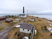 Tower of Sorve lighthouse and buildings on peninsula of Baltic sea. Spring season. Saaremaa, Estonia, Europe. Tower of Sorve lighthouse and buildings on Royalty Free Stock Images