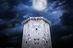 Tower of castle at night in the moonlight. Tower of stone castle at night in the moonlight stock image