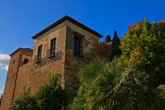 Tower, detail of Alcazaba moorish castle in Malaga. Tower surrounded by green plants, detail of Alcazaba moorish castle in Malaga, on a sunny day with clear blue Royalty Free Stock Image