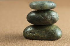 Tower of three dark stones. On brown sand Stock Photos