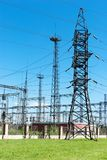High voltage line. Tower for transmission electricity on green grass summer time Stock Photography