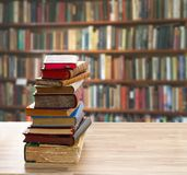 Pile of old books. Tower of vintage books with open one on wooden shelf in library royalty free stock images