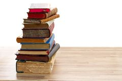 Pile of old books. Tower of vintage books with open one on wooden shelf over white background royalty free stock photo