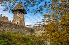 Tower and wall of Nevytsky Castle. Nevytsky Castle, Ukraine - October 27, 2016: tower with wooden roof and stone wall of fortress on grassy hillside among forest Stock Photography