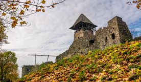 Tower and wall of Nevytsky Castle. Nevytsky Castle, Ukraine - October 27, 2016: tower with wooden roof and stone wall of fortress on grassy hillside among forest Stock Image