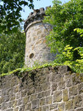 Tower and wall of old German castle. Tower and wall of German castle between trees royalty free stock photography