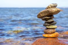 Tower of wet stones on sea beach background stock photo