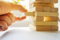 The tower from wooden blocks. And man's hand take one block. The game of dice close-up Stock Photos