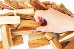 The tower from wooden blocks and man`s hand take one block royalty free stock photos