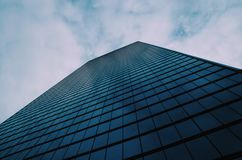 Towering building against clouds. Large glass building towering toward a partly cloudy sky Stock Photos