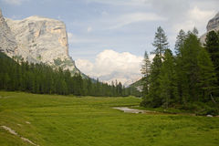 Towering Cliffs of the Dolomites. A serene valley in the Dolomites of Northern Italy surrounded by giant stone monoliths and calm streams Stock Image