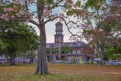 The Queen`s Royal College taken from the western side of the Queen`s Park Savannah in Port-of-Spain, Trinidad one early morning. The towering clock of the Queen` Stock Photos