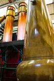 Huge Copper Distillation Machines in Bright Gold and Orange Colo. Towering colorful copper distillation stills in whisky warehouse Royalty Free Stock Image