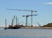 Towering CRANES at the construction site by the sea Stock Image