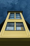 Towering house. Detail of a yellow house against a blue sky royalty free stock image