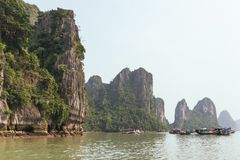 Towering limestone islands over emerald water with growing trees on it that view from cruising tourist boat in summer. Towering limestone islands over emerald Stock Images