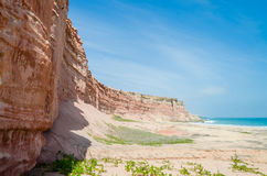 Towering red sandstone cliffs at Angola`s coast line. Of the Namib Desert Royalty Free Stock Image